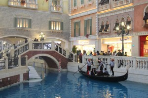 Macau - real boat on a fake river surrounded by fake houses under fake blue sky; all on 2nd or 3rd floor of some casino.